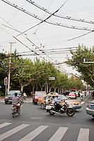 police motorbike plus local traffic negotiate busy cross roads in shanghai china