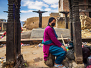 04 MARCH 2017 - KATHMANDU, NEPAL: A woman sits among the wreckage at Swayambhu Stupa. The stupa was badly damaged in the 2015 Nepal earthquake. Recovery seems to have barely begun nearly two years after the earthquake of 25 April 2015 that devastated Nepal. In some villages in the Kathmandu valley workers are working by hand to remove ruble and dig out destroyed buildings. About 9,000 people were killed and another 22,000 injured by the earthquake. The epicenter of the earthquake was east of the Gorka district.     PHOTO BY JACK KURTZ
