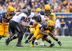 Nov 23, 2019; Morgantown, WV, USA; West Virginia Mountaineers running back Kennedy McKoy (6) runs the ball and is tackled by Oklahoma State Cowboys defensive end Trace Ford (94) during the first quarter at Mountaineer Field at Milan Puskar Stadium. Mandatory Credit: Ben Queen-USA TODAY Sports