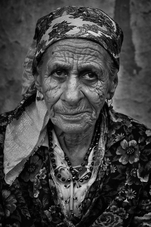 An elderly Roma woman with furrowed face and head scarf in the all-Roma village of Poiana Negustiorului in Bacau County, Romania.