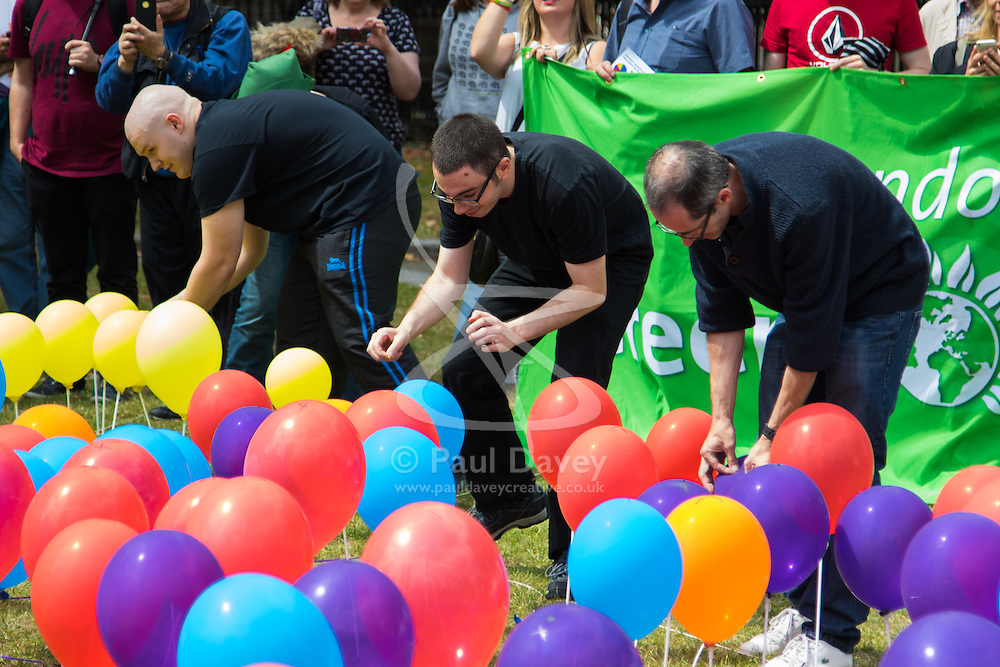 Old Palace Yard, Westminster, July 25th 2015. Protesters gather outside the Houses of Parliament to demand electoral reform, including proportional representation rather than the first-past-the-post method that saw the Tories gain a majority. PICTURED: Balloons representing the votes to minor parties are popped to show the scale of non-representation in the last general election.