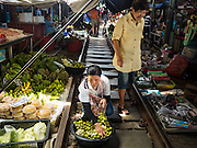 27 SEPTEMBER 2016 - BANGKOK, THAILAND: A woman walks past a woman selling limes in the market in the train station in Samut Songkhram. The train from Baen Laem to Samut Songkhram (Mae Khlong) recently resumed service. The 33 kilometer track was closed for repair for almost a year. In Samut Songkhram, the train passes over the market. Vendors pull their stands out of the way and people step out of the way as the train passes through the market. It is one of the most famous train stations in Thailand and has become an important tourist attraction in the community.     PHOTO BY JACK KURTZ