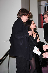OSCAR BURNETT and ASSISI JACKSON daughter of Jade Jagger at a party hosted by Prada to celebrate launch of a book documenting the company's diverse projects in fashion, architecture, film and art held at their store 16/18 Old Bond Street, London on 19th November 2009.