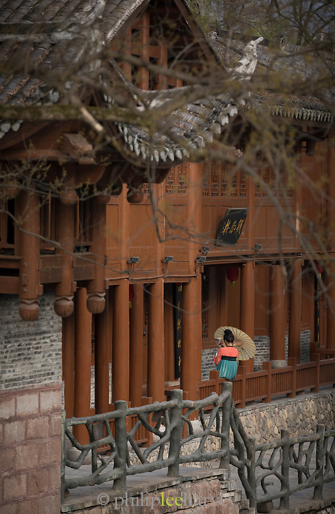 Ancient wooden Chinese architecture and a distant view of a woman in a traditional dress with an umbrella, Fenghuang, Hunan Province, China