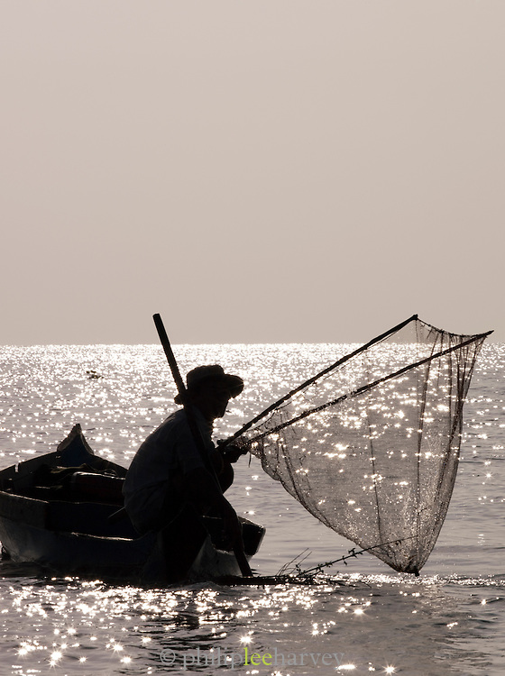 Silhouette of a man fishing with his net on the great Tonlé Sap lake, Cambodia