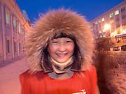 Junge jakutisch Frau mit Kopfbedeckung geschützt gegen die extreme Kaelte in der Innenstadt von Jakutsk. Jakutsk wurde 1632 gegruendet und feierte 2007 sein 375 jaehriges Bestehen. Jakutsk ist im Winter eine der kaeltesten Grossstaedte weltweit mit durchschnittlichen Winter Temperaturen von -40.9 Grad Celsius. Die Stadt ist nicht weit entfernt von Oimjakon, dem Kaeltepol der bewohnten Gebiete der Erde.<br /> <br /> Young Yakut women protected with headgears against the extrem climate  in the city center of Yakutsk. Yakutsk was founded in 1632 and celebrated 2007 the 375th anniversary - billboard announcing the celebration. Yakutsk is a city in the Russian Far East, located about 4 degrees (450 km) below the Arctic Circle. It is the capital of the Sakha (Yakutia) Republic (formerly the Yakut Autonomous Soviet Socialist Republic), Russia and a major port on the Lena River. Yakutsk is one of the coldest cities on earth, with winter temperatures averaging -40.9 degrees Celsius.