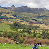 South America, Ecuador.  A local man sits on the roadside of the Pan-American Highway which weaves through the Andes of Ecuador.