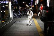 SAPPORO, JAPAN - 5 SEPTEMBER - A man wearing white trousers and white shirt in the sapporo street near Susukino. [FR] Un homme portant une tenue blanche , un chapeau et des lunettes de soleil dans les rues de Susukino a Sapporo