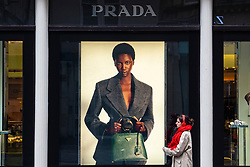Woman walks past window display for Prada in Frasers department store, Glasgow, Scotland, UK