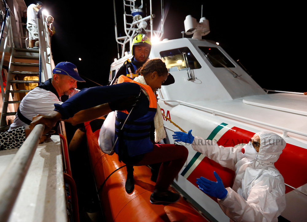 Rescued migrants climb onto a Italian Coast Guard vessel from the Migrant Offshore Aid Station (MOAS) ship MV Phoenix between Libya and the Italian island of Lampedusa, August 3, 2015.  Some 118 migrants were rescued by the MOAS ship MV Phoenix from a rubber dinghy around 20 miles (32 kilometres) off the coast of Libya on Monday morning. The Phoenix, manned by personnel from international non-governmental organisations Medecins san Frontiere (MSF) and MOAS, is the first privately funded vessel to operate in the Mediterranean.<br /> REUTERS/Darrin Zammit Lupi <br /> MALTA OUT. NO COMMERCIAL OR EDITORIAL SALES IN MALTA