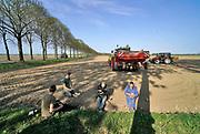 Nederland, Batenburg, 17-4-2020 Een boer, loonwerker, poot aardappels. Het gebeurt automatisch via een ingenieus mechaniek achter de tractor. De grond is droog door het drie weken uitblijven van regen. Het is even pauze en dan eten ze een frietje . Foto: Flip Franssen