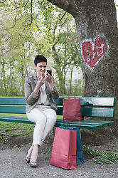 Mature woman applying lipstick for her dating at park, Bavaria, Germany