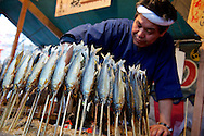 Whole fish grilled on bamboo skewers at a stall in Kyoto during sakura, the cherry blossom. Japan 2013