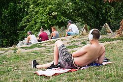 Men relaxing at weekend in bohemian Mauer Park in Prenzlauer Berg in Berlin Germany