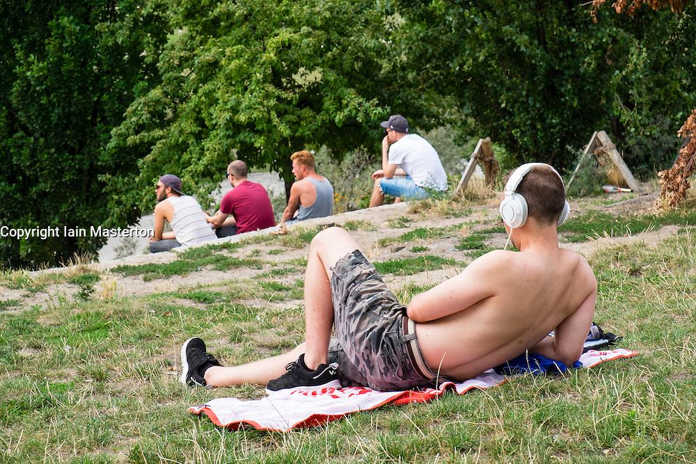 Men relaxing at weekend in bohemian Mauer Park in Prenzlauer Berg in Berlin Germany