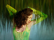 Woman in a yellow green dress folds her arms behind her as a wall of grass comes down from behind her.  Photo-Montage