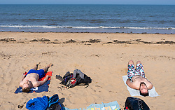 Portobello, Scotland, UK. 25 April 2020. Views of people outdoors on Saturday afternoon on the beach and promenade at Portobello, Edinburgh. Good weather has brought more people outdoors walking and cycling. Police are patrolling in vehicles but not stopping because most people seem to be observing social distancing. Two men sunbathing whilst exercising social distancing on the beach.  Iain Masterton/Alamy Live News