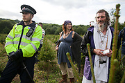 Police and druids in a field of baby Christmas trees. Anti-fracking activists join hands to surround the Cuadrilla fracking site. Thousands turned out for a march of solidarity against fracking in Balcombe. The village Balcombe in Sussex is the  centre of fracking by the company Cuadrilla. The march saw anti-fracking movements from the Lancashire and the North, Wales and other communities around the UK under threat of gas and oil exploration by fracking.