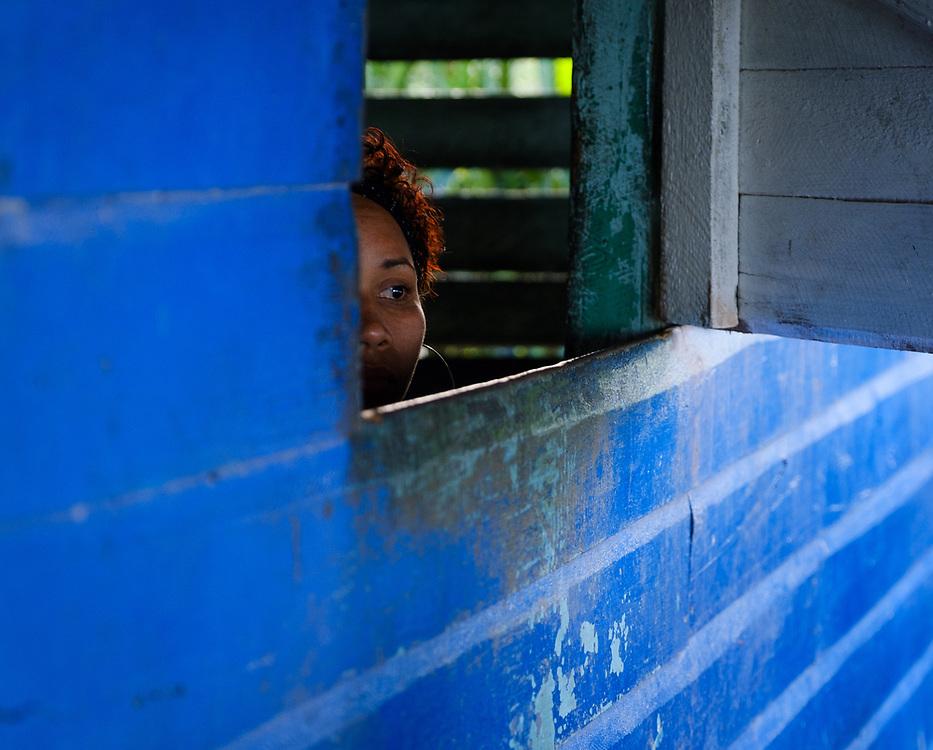 BARACOA, CUBA - CIRCA JANUARY 2020:  Cuban woman looking from a window at the Restaurant Tato in Manglito Beach, a popular beach close to Baracoa in Cuba.