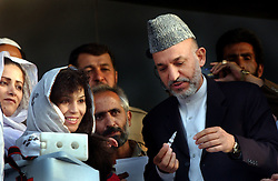KABUL,AFGHANISTAN - SEPT. 2: Afghan President Hamid Karzai, together with representatives of the Ministry of Public Health, WHO and UNICEF kicked off a three-day nation wide immunisation campaign against polio by administering the first  drops of the Oral Polio Vaccine to an unidentified Afghan child, September 2, 2002 in Kabul, Afghanistan.  The latest campaign will target 5.9 million children under the age of five and teams of vaccinators will go from village to village to ensure that all children in that age bracket are immunised.  (Photo by Ami Vitale/Getty Images)