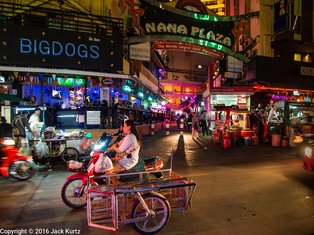 """03 NOVEMBER 2016 - BANGKOK, THAILAND:   Traffic goes past the darkened main entrance to Nana Plaza, one of Bangkok's most famous """"adult entertainment districts."""" Bangkok's infamous nightlife has been scaled back during the mourning period for the late Bhumibol Adulyadej, King of Thailand. The revered King died on 13 October 2016 at age 88. The government declared a year of mourning. The government ordered Thailand's notorious adult entertainment districts to turn off their neon lights, dress employees in black and ensure that music can't be heard on the street in front of the venues for 30 days, the government said the entertainment venues could resume normal operations on 14 November.      PHOTO BY JACK KURTZ"""