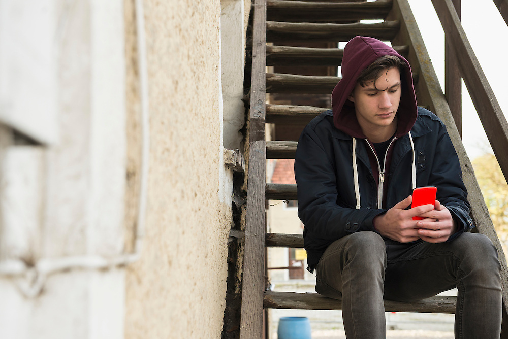 Young man text messaging on smart phone and sitting on wooden stairs, Munich, Bavaria, Germany