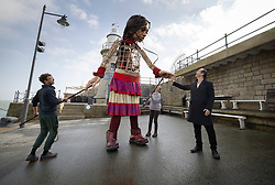 © Licensed to London News Pictures. 19/10/2021. Folkestone, UK. British actor Jude Law (R) greets Little Amal, a giant puppet, as she performs on the Harbour Arm at Folkestone in Kent. The 3.5m tall puppet, worked by a team of puppeteers, has been on a journey starting from Turkey in July, visiting Greece, Italy, Switzerland, Germany, Belgium and France.  Little Amal, whose name means hope in Arabic, represents the journey of a nine year old girl from Syria. Photo credit: Peter Macdiarmid/LNP