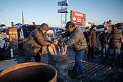 """Activists Dimi (left) and Bosch are preparing a fire for heating at the barrikades blockading a building supplies store named """"Epicenter"""" in the city of Lviv, Ukraine. Two people passing by."""