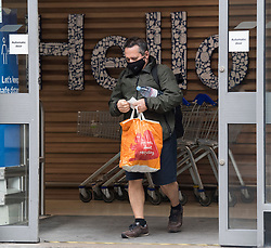 © Licensed to London News Pictures. 24/07/2020. London, UK. A shopper leaves Tesco on Goodge Street in central London wearing a face mask, on the day that the wearing of mask in shops becomes compulsory. The UK Government has published formal guidance on spaces where the wearing of masks will now be mandatory, including in shops, supermarkets and shopping centres. Photo credit: Ben Cawthra/LNP