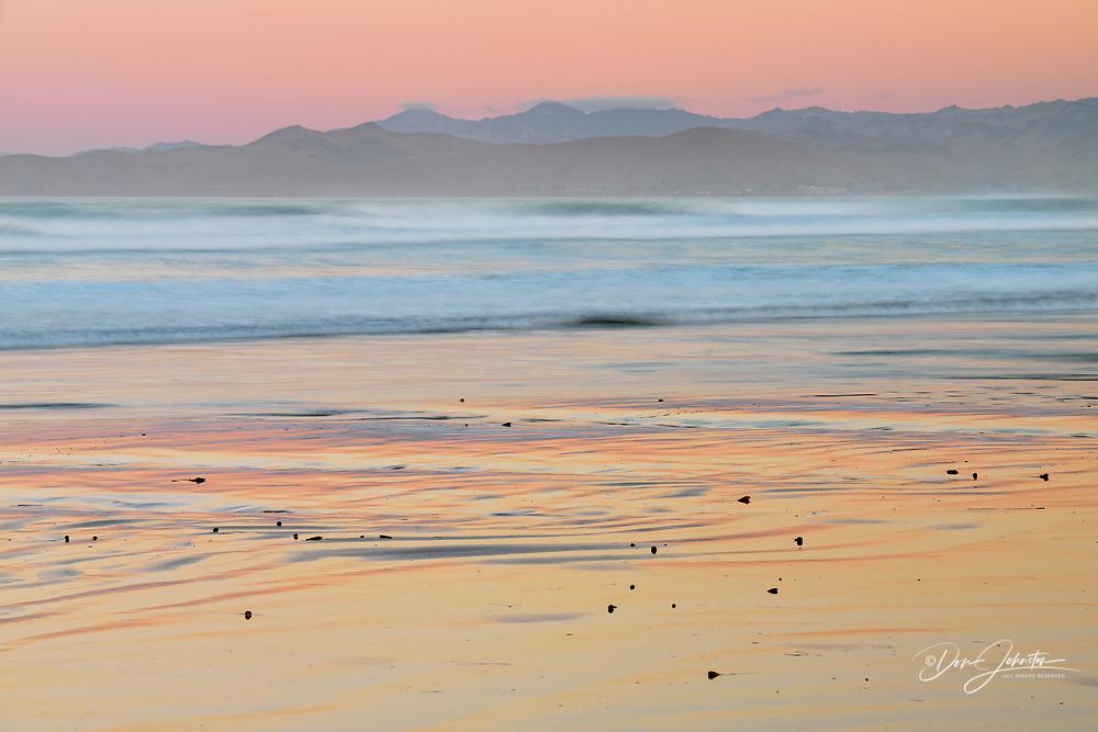 Surf and sunrise colours over Morro Rock beach, Morro Bay, California, USA