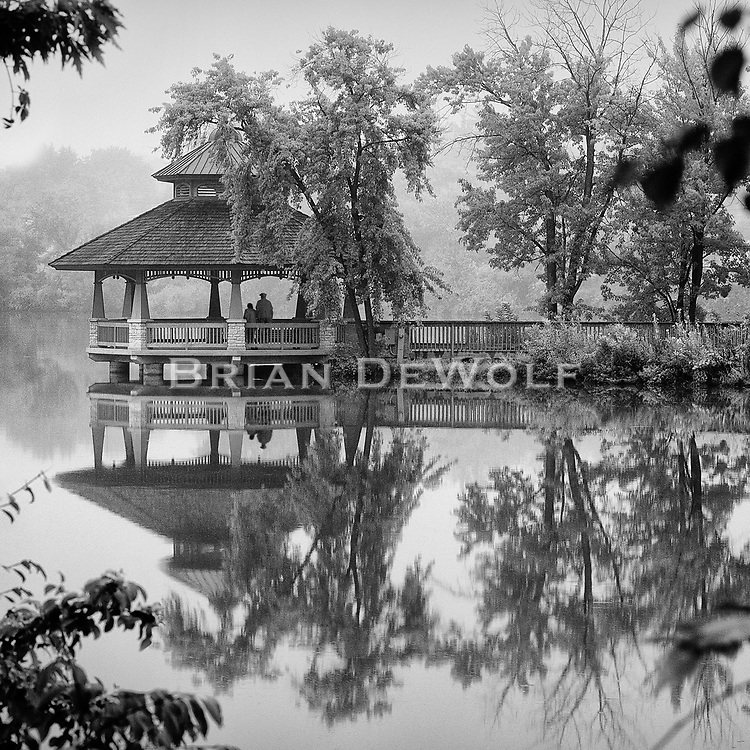"""This is an open edition print. Canvas prints have a 2 inch black border so it can be gallery wrapped. The print is made using pigmented inks on museum-grade canvas or watercolor paper. Each print also gets a light coating of lacquer protective spray. Each print is hand signed by Brian DeWolf. A man and woman in the gazebo in Batavia, Illinois are looking out upon the Fox River. The reflections are in the area that leads to the cove. Aspect ratio is 1""""w x 1""""h."""