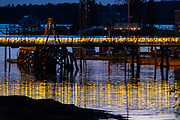 Thousands of holiday fairy lights decorate the historic footbridge across Boothbay Harbor, Maine. The 1,000 foot wooden pedestrian bridge that connects one side of the harbor to the other is decorated for Christmas as part of the annual Boothbay Lights Festival.