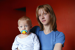 Portrait of a young stressed mother with her baby,