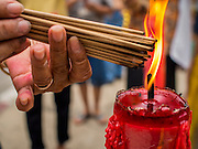 """07 AUGUST 2014 - BANGKOK, THAILAND:  A person lights candles before praying at Pek Leng Keng Mangkorn Khiew Shrine. Thousands of people lined up for food distribution at the Pek Leng Keng Mangkorn Khiew Shrine in the Khlong Toei section of Bangkok Thursday. Khlong Toei is one of the poorest sections of Bangkok. The seventh month of the Chinese Lunar calendar is called """"Ghost Month"""" during which ghosts and spirits, including those of the deceased ancestors, come out from the lower realm. It is common for Chinese people to make merit during the month by burning """"hell money"""" and presenting food to the ghosts. At Chinese temples in Thailand, it is also customary to give food to the poorer people in the community.       PHOTO BY JACK KURTZ"""