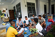 A group of palm oil smallholder farmers sit with Imam El Marzuq from the Roundtable on Sustainable Palm Oil 3rd from left, on the veranda of a house Ukui, Riau Province, Indonesia, on 15 June 2015. This area has become dominated by palm oil production, and some smallholder farmers have formed co-operatives to share costs, increase access to markets, and become certified by the Roundtable on Sustainable Palm Oil. He is part of Amanah, a local cooperative that has helped over 400 farmers become RSPO certified - reducing their use of pesticides and fertilizers, increasing yields, and improving farm management.