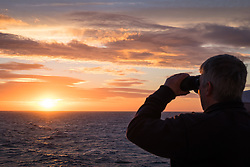 © Licensed to London News Pictures. 29/11/2016. Wick, UK.  A man looking out to sea through binoculars during sunrise on a cold and windy morning in the Moray Firth today, 29th November 2016. Photo credit: Rob Arnold/LNP