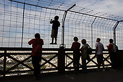 A young tourist climbs up the fence to admire Paris below from the second level of the Eiffel Tower. With other adults alongside who look at distant landmarks, they offer no advice on safety as the child climbs above their heads. The Eiffel Tower (nickname La dame de fer, the iron lady) is a puddled iron lattice tower standing 320 metres (1,050 ft) tall, about the same height as an 81-story building. It is located on the Champ de Mars in Paris, named after the engineer Gustave Eiffel, whose company designed and built the tower. Erected in 1889 as the entrance arch to the 1889 World's Fair, it has become both a global cultural icon of France and one of the most recognizable structures in the world.
