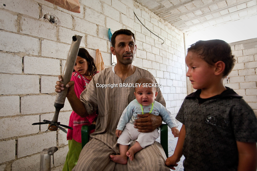 Hasan, a resident of Lejj, Idlib, displays a rocket fired near his home from a Syrian military helicopter. His house was raided, his livestock killed and home burnt when the Syrian military and shabiha loyal to the regime arrived in his village. He, his wife and their three children have nothing apart from the clothes they are wearing after the attack three days previously. 16/06/2012