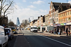 © Licensed to London News Pictures. 26/03/2015. London, UK. View along Whitechapel Road in east London on 23rd March 2015, with the Gerkin and City of London in the background. Whitechapel was today named as having the most unhealthy high street in London in a report by the Royal Society for Public Health. Image date 23rd March 2015. Photo credit : Vickie Flores/LNP