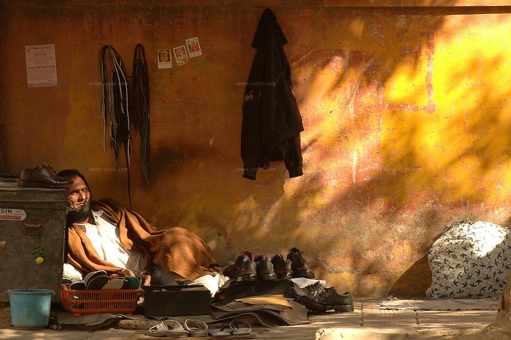 A shoemaker basking in the winter sun on the street of New Delhi