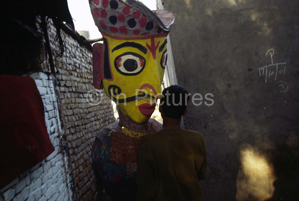 A performer carries a giant puppet through the lanes of Shadipur<br /> The Kathiputli Colony in the Shadipur Depot slum is home to hundreds of (originally Rajasthani) performers. The artistes who live here - from magicians, acrobats, musicians, dancers and puppeteers are often international renowed by always return to the Shadipur slum.