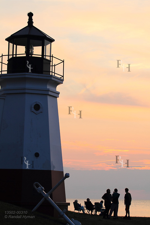 Lighthouse towers over beachgoers at sunset on Lake Erie at Vermilion, OH.
