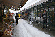 Vienna, Austria. A shop owner at the Naschmarkt tries to get rid of the snow..On 1/17/2013, 30+ centimeters of snow fell in Vienna, slowing down many aspects of public life.