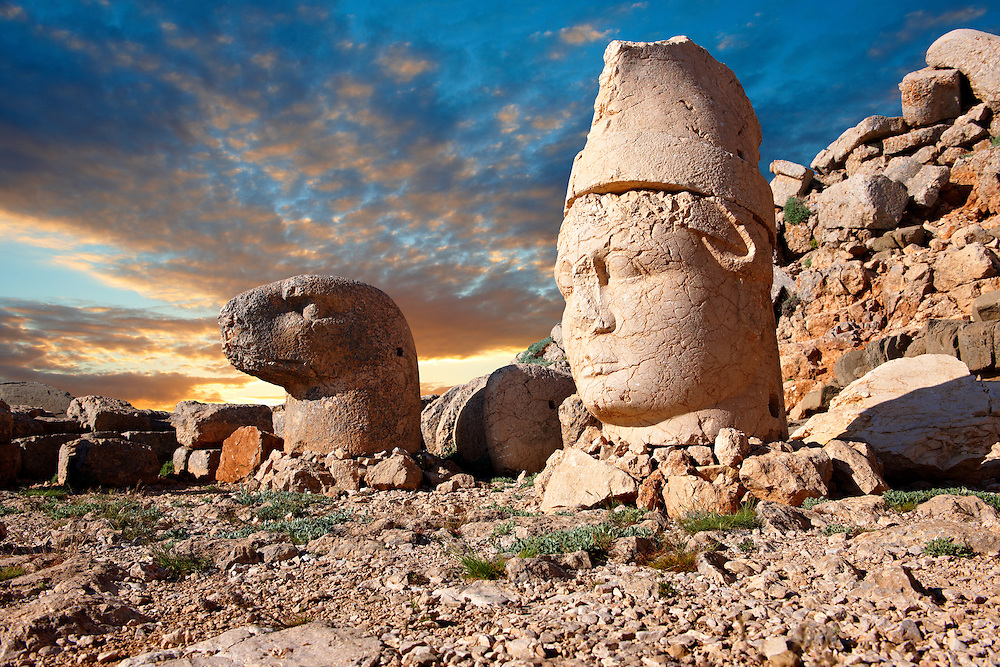Pictures of the statues of around the tomb of Commagene King Antochus 1 on the top of Mount Nemrut, Turkey. Stock photos & Photo art prints. In 62 BC, King Antiochus I Theos of Commagene built on the mountain top a tomb-sanctuary flanked by huge statues (8–9 m/26–30 ft high) of himself, two lions, two eagles and various Greek, Armenian, and Iranian gods. The photos show the broken statues on the  2,134m (7,001ft)  mountain. 7