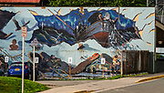A sea-themed mural in Juneau, capital city of Alaska, USA. The City and Borough of Juneau is the capital city of Alaska and the second largest city in the USA by area (only Sitka is larger). This unified municipality lies on Gastineau Channel in the Alaskan panhandle. Juneau has been the capital of Alaska since 1906, when the government of what was the District of Alaska was moved from Sitka. The city is named after a gold prospector from Quebec, Joe Juneau. Isolated by rugged terrain on Alaska's mainland, Juneau can only be reached by plane or boat. Downtown Juneau sits at sea level under steep mountains up to 4000 feet high, topped by Juneau Icefield and 30 glaciers.