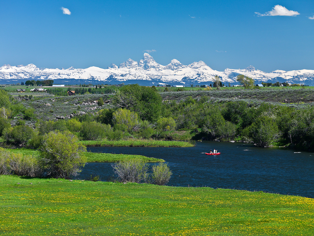 Two people float down the Henrys Fork of the Snake River near Ashton, Idaho on a perfect summer day with the snow covered Teton Mountain Range in background. Licensing and Open Edition Prints