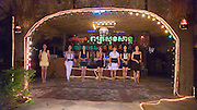 SEX INDUSTRY TOURISM. South East Asia, Cambodia, Phnom Penh. Taxi girls, prostitutes, serve foriegn tourists & Khmer, Cambodians. The sex industry is part of the fabric, servicing all classes of Cambodian society. Girls are forced into prostitution because of poverty and corruption that exists across the country. People might earn 1 to 2 $ per day, even less in rural areas, so the lure of prostitution is high. Families can sell young girls, virgins, for several hundred dollars. Cheap brothels line the streets in parts of the city centre, near railway tracks, and on the periphery. Sex for Cambodians at cheap prices in the street brothels, as low as 1 $ US, to exorbitant fees in penthouse hotel suites for the rich. Sex tourism industry attracts Western and Asian tourists typically paying 10 - 30 $ US. Expressions such as 'yam yam', eating, for a blowjob 'bam bam' for intercourse. There are 'lady-boys', youths, who use the money to pay for  sex change operations. Prostitutes spend lots of money on make-up, clothes, and mobile telephones. They live in squalor. Due to public advertising campaigns and outreach work, Aids and HIV cases have dramatically decreased, in Cambodia, since the late '90s. Condoms are encouraged, are cheap and widely available. This is seen as  a success story by medical and health authorities. There are risks as ex-prostitutes known as 'sweethearts' don't use condoms with their partners. Brothels, v & madams take their cut, but many taxi-girls work as free agents. Bars, pool halls or beer gardens have staff and taxi-girls available to service male clients, some work as barmaids or escorts. There is violence against prostitutes; gang-rape and murder by Khmer gangs. Once a girl has worked as a prostitute it is unlikely she can ever marry.///Girls singing karaoke in a beer garden, hoping that a client will want to buy their services as an escort or prostitute during the evening soiree.