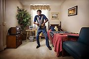 An elderly african-american musician dances and sings in his bedroom.