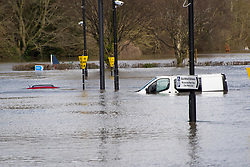 © Licensed to London News Pictures. 25/02/2020. Shrewsbury, Shropshire, UK. A red car is almost completely submerged at the Guildhall Riverside carpark as the River Severn levels continue to rise at Shrewsbury in Shropshire, UK causing severe flood disaster situation. The Environment Agency forecast levels to peak soon. The level at 12.45 hrs at Welsh Bridge was 5.07 metres. Photo credit: Graham M. Lawrence/LNP