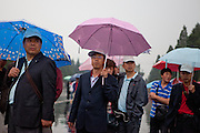 """A group of tourists with umbrellas entering during a rainy day the area at """"The Temple of Heaven"""" which is a complex of Taoist buildings situated in the southeastern part of central Beijing. Beijing is the capital of the People's Republic of China and one of the most populous cities in the world with a population of 19,612,368 as of 2010."""
